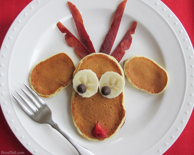 Simple Breakfast Recipe: Reindeer Christmas Pancakes - This simple breakfast recipe for Reindeer Christmas pancakes is easy to make and looks adorable! Imagine all of Santa's elves lining up for a delicious breakfast of fluffy reindeer pancakes before they head out for a tough day at the toy factory. The batter is made with Greek yogurt and honey, making them healthy but still sweet enough to eat with or without syrup.