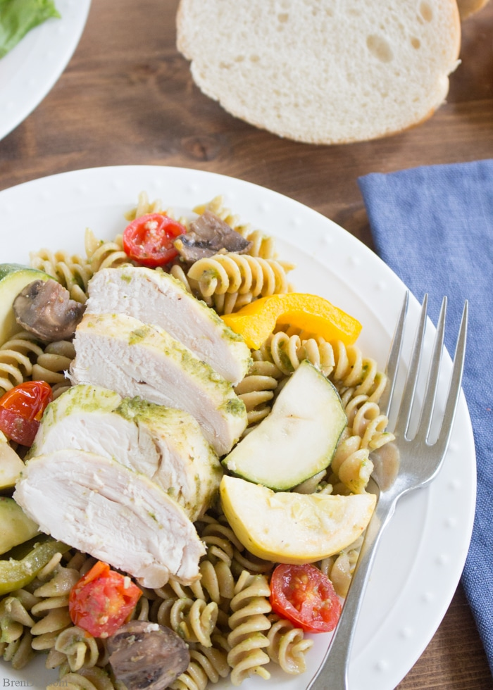 Chicken Pesto Pasta Easy Crockpot Recipe: This throw & go crock pot recipe features basil pesto, chicken, roast vegetable, and chicken. Serve it with pasta for a healthy and tasty dinner that takes just minutes to prepare.