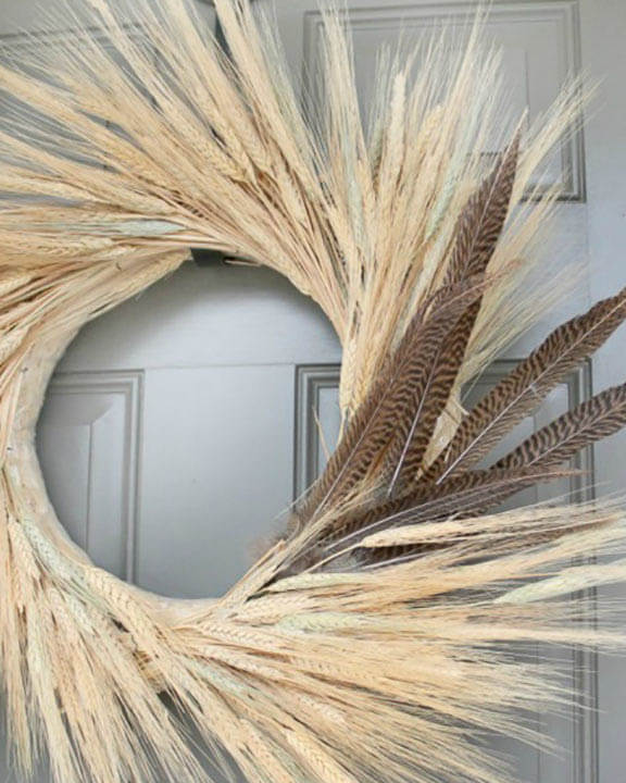 fall wreath made from wheat and feathers