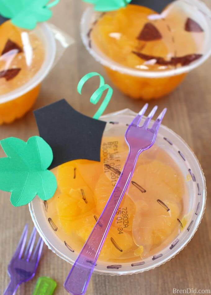 orange fruit cup decorated to look like pumpkin with fork