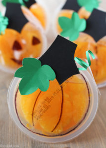 orange fruit cup decorated to look like pumpkins